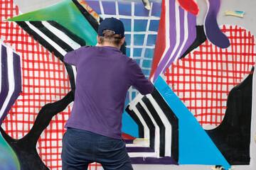 Graffiti artist  paints colorful graffiti on wall.