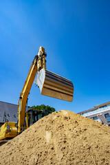 Gelber Bagger mit Baggerschaufel für Sand