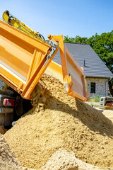 Oranger Muldenkipper kippt Sand auf Baustelle im Neubaugebiet ab