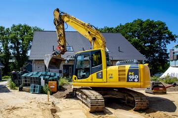 Komatsu-Bagger auf Baustelle in Wohngebiet Neubaugebiet