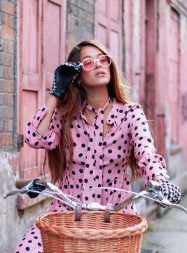 Portrait Of Model In Pink Dress And Gloves On A Bicycle In London
