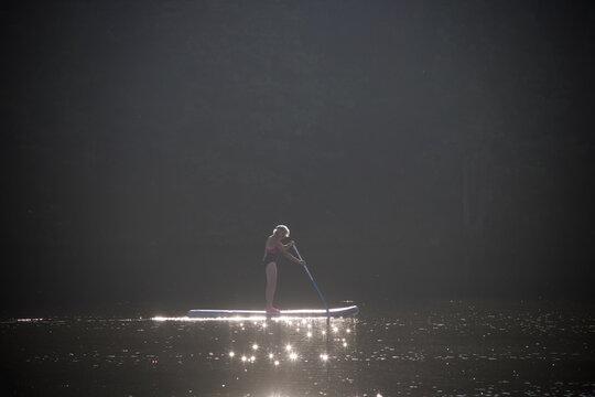 Woman Paddleboarding On Lake