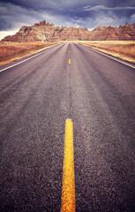 Photo sur Plexiglas Saumon Asphalt road in Badlands National Park, focus on yellow lane, travel concept, color toning applied, USA.