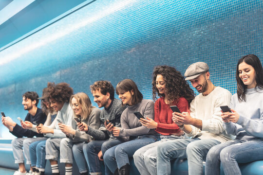 Friends Using Smart Phones While Sitting On Seat