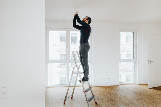 Home Owner Standing On Ladder Fixing Light Installation