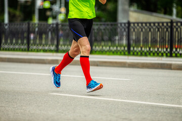 Wall Mural - legs male runner in bright red compression socks run down street race