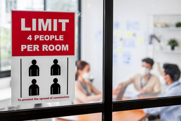 Limit people in meeting room sign over asian business people wear face mask working and meeting in...