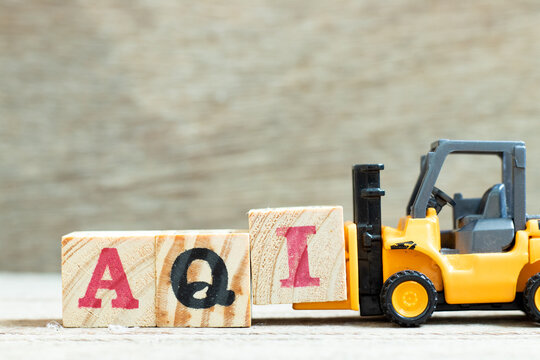 Toy forklift hold letter block I to complete word AQI (Air quality index)on wood background