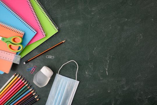 School educational supplies on green blackboard mask protection top