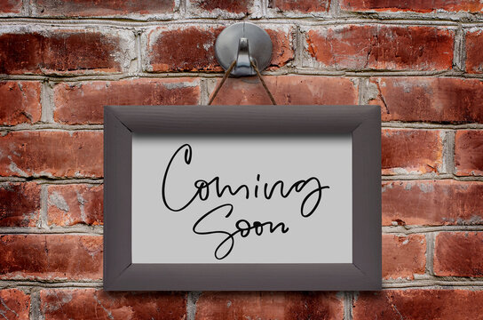 Coming soon. Handwritten inscription in a wooden frame. Brown brick wall