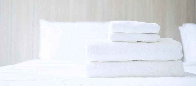 Stack of white towel and Bathrobe on bed in luxury hotel or resort. Laundry, Relax, holiday, spa, massage and vacation concepts