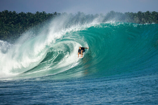 Surfer on perfect blue big tube wave, empty line up, perfect for surfing, clean water, Indian Ocean in Mentawai islands