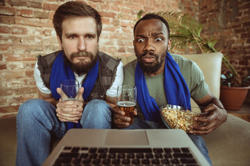 Excited football fans watching sport match at home, remote support of favourite team during...
