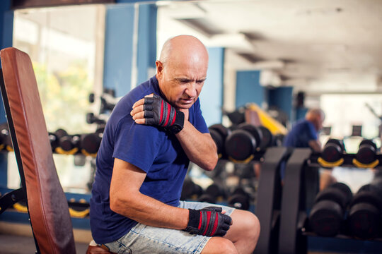 A portrait of senior man feeling strong shoulder pain during training in the gym. People, healthcare and lifestyle concept