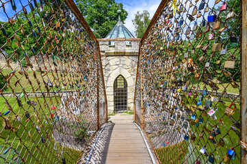 Bridge with many Love locks leading to small Roundhouse in pond in Bojnice castle park (Bojnice, Slovakia)