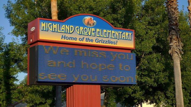 """Redlands, CA / USA - July 12, 2020: Electronic sign at a California school reads """"We miss you and hope to see you soon"""". Fall 2020 reopening is doubtful."""