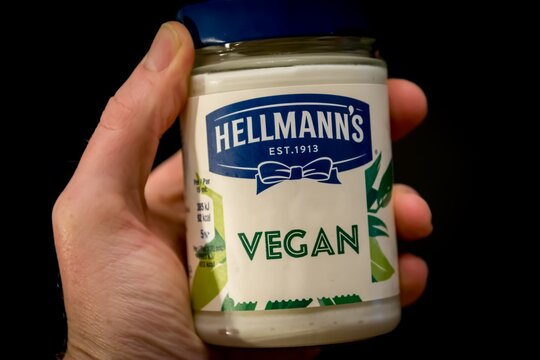 ANTWERP, BELGIUM - Nov 15, 2019: Hand holding Hellmann's Vegan and plant-based mayonnaise spread on black background