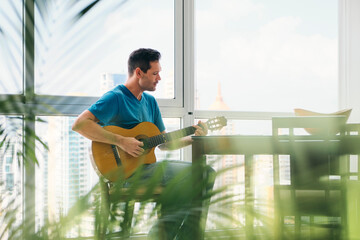 Portrait Of Man Playing Classic Guitar And Singing At Home