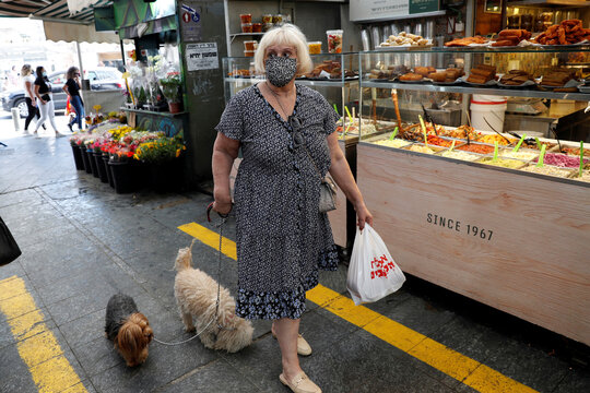 A woman wears a face mask as she walks with her dogs in a main market in Jerusalem