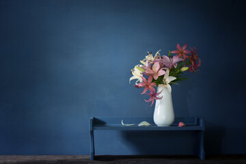 bouquet of lily flowers in vase on dark background