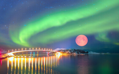 Sommaroy Bridge is a cantilever bridge connecting the islands of Kvaloya and Sommaroy with full moon and Aurora Borealis - Hillesoy Tromso Norway