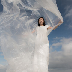 Girl in white dress with plastic drape waving in the wind under a blue sky