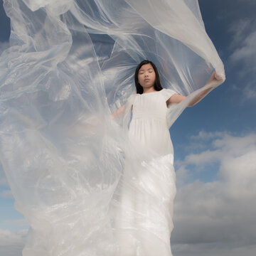 Teenage girl with eyes closed covered in white plastic sheet standing outdoors