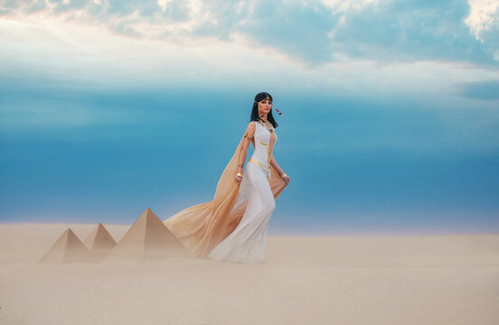 young beautiful woman model image Queen Cleopatra walks in desert Egyptian pyramids. Creative retro traditional gold jewelry bob hair cut. White satin long vintage dress, orange silk cape fly train