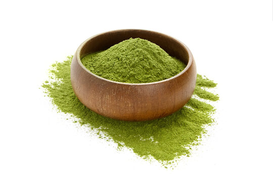 Dried organic wheatgrass powder in wooden bowl isolated on white.