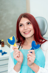 A woman demonstrates the result of casts of her teeth on a spoon with silicone material