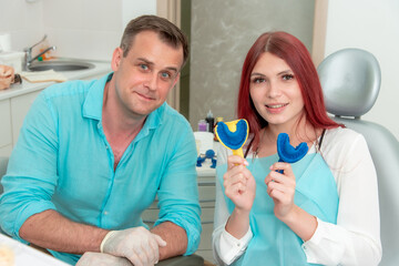 Happy doctor orthodontist with his patient demonstrate the result of impressions of her teeth on a spoon with silicone material