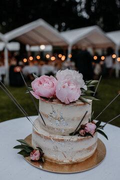 Naked Cake als Hochzeitstorte mit Pfingstrosen und Lichtern im unscharfen Hintergrund
