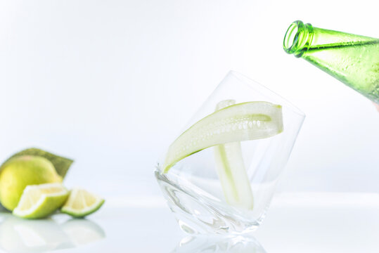 An empty glass with green sparkling water bottle  and lime fruits on a white background, close up, isolated