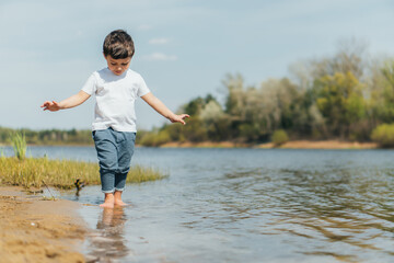 selective focus of cute boy standing in pond