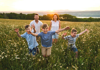 Happy family on daisy field at the sunset having great time together running together
