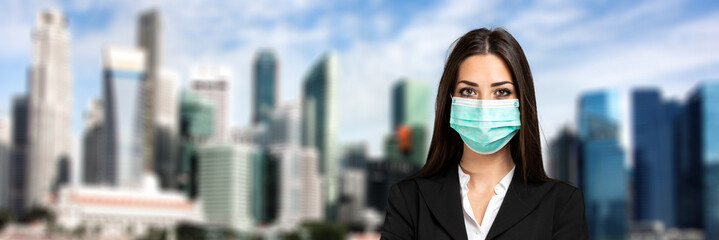 Confident young female manager outdoor in a modern urban setting wearing a mask, coronavirus concept