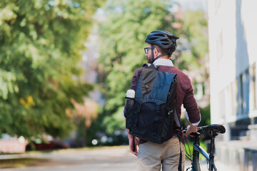 Male commuter or messenger with a bike in urban background. Safe cycling in the city, going to work by bicycle, delivery man image