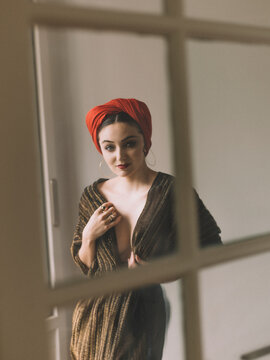 Woman with retro look and red turban behind a window