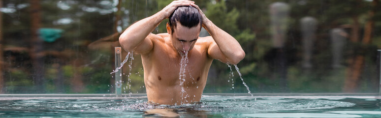 Foto op Plexiglas Spa panoramic concept of wet and muscular man touching hair in swimming pool