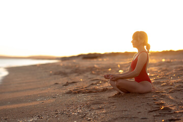 Young beautiful girl in a red bathing suit sits on the seashore in lotus position. Yoga. Healthy lifestyle. Meditation