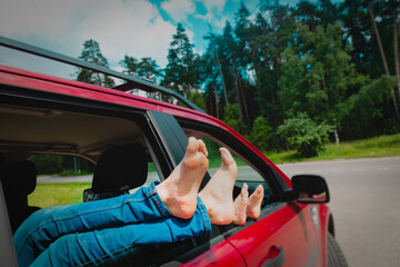 feet of happy kids travel by car in summer nature