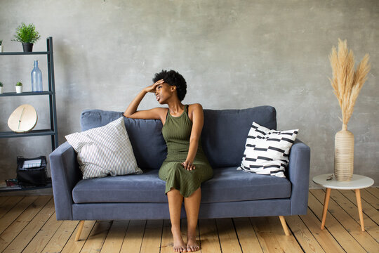 Unhappy African American woman sit on the sofa, the girl is very upset sitting on the couch of her apartment.