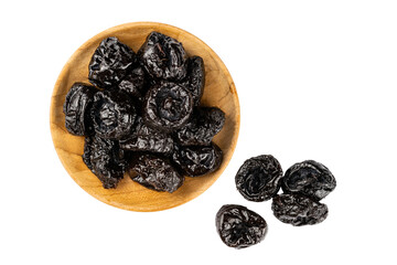 Fototapete - Top view of dried pitted prunes in wooden plate and prunes on the floor over white background.
