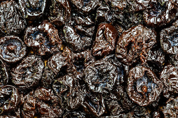 Fototapete - Top view of pitted prunes on wooden board. Prunes are 64% carbohydrates including dietary fiber, 2% protein, a rich source of vitamin K, and a moderate source of B vitamins and dietary minerals.