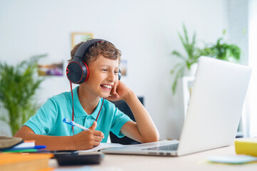 cheerful boy with headphones uses laptop to make a video call with his teacher.