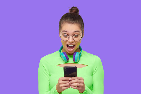 Young girl holding phone in hands and looking at screen with surprised face, shocked by content, isolated on purple background