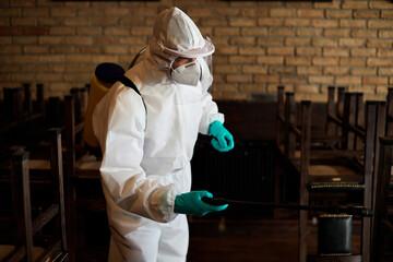 Fototapeta Sanitation worker in protective suit disinfecting empty cafe during coronavirus epidemic.