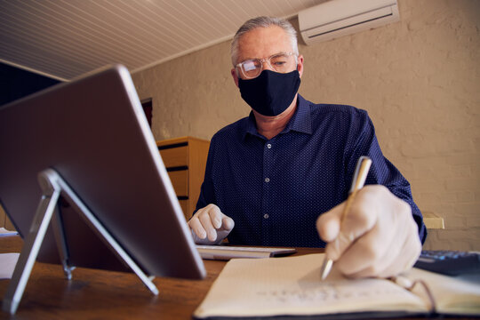 Businessman working at desk wearing a face mask