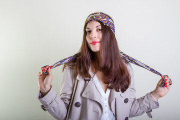 A beautiful fashionable woman in a light raincoat and bandana poses on a light background.