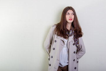 Portrait of a happy young woman in a light raincoat against a white wall.